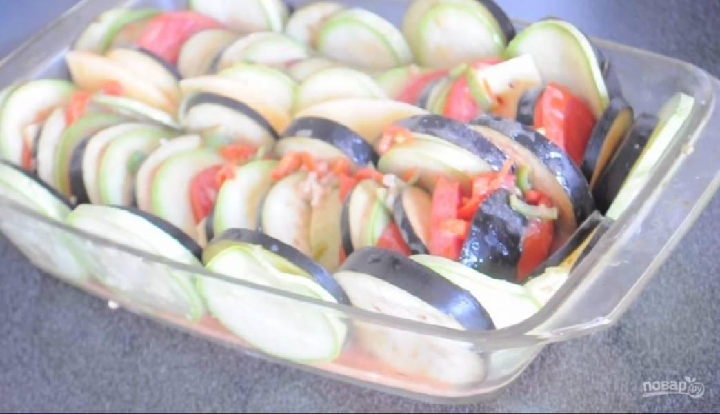 2. Выложите в форму для запекания поочередно баклажаны, кабачки, сыр и помидоры, формируя рататуй. Свободное место в форме заполните оставшимися овощами.