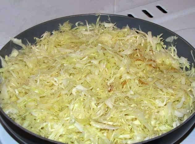 Нашинкуйте капусту и обжарьте в течение 5 минут на сковороде. Затем добавьте 0,5 стакана воды и тушите еще 7-8 минут до готовности.