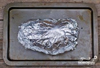 Противень с мясом ставлю в разогретую духовку. Выпекаю свинину в течение 20 минут при температуре 180 градусов. Затем снижаю температуру до 160 градусов и готовлю еще полтора часа. Если вы запекаете кусок мяса весом больше, чем 2 килограмма, то добавляйте по 20 минут на каждый килограмм веса. Запеченный окорок вынимаю. Даю ему время остыть, затем приоткрываю фольгу и аккуратно сливаю весь жир.