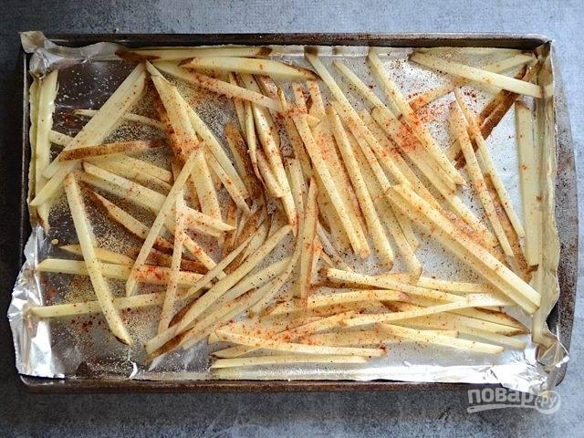 3.Два противня застелите фольгой и полейте несколькими каплями растительного масла. Выложите картофель в один слой на каждый. Полейте картофель оставшимся растительным маслом, разделите между ними специи и соль.