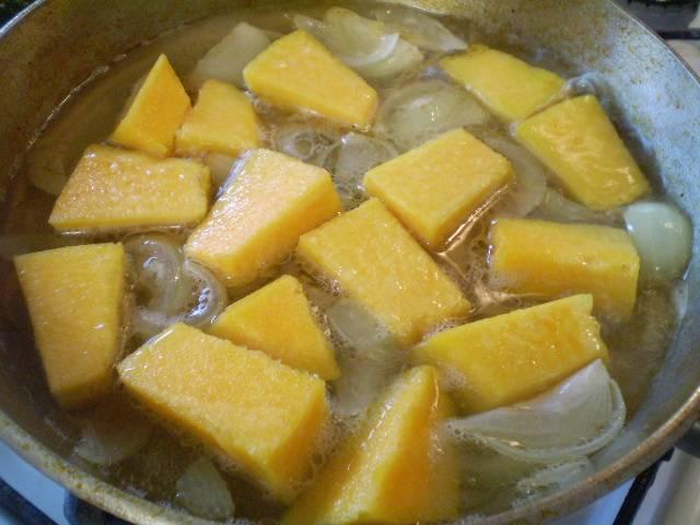 Влейте бульон или воду, добавьте тыкву. Тушите 20 минут под крышкой.