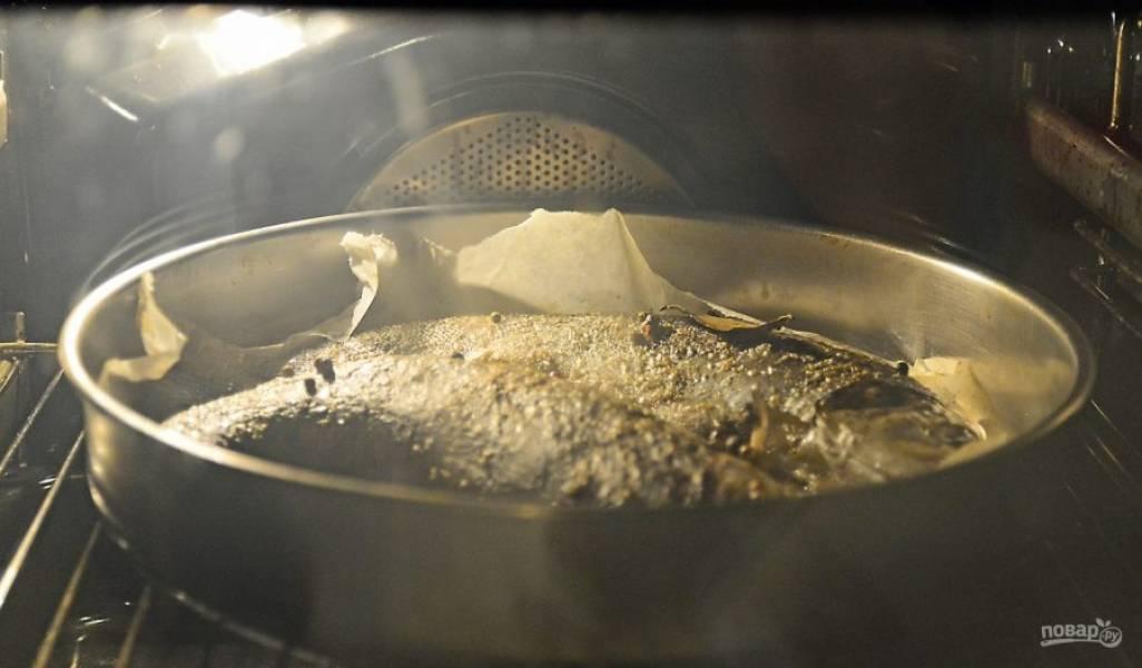 Духовку прогрейте до 200 градусов. Накройте рыбу пергаментом и отправьте запекаться на 40 минут. Затем снимите бумагу и готовьте еще 15 минут.