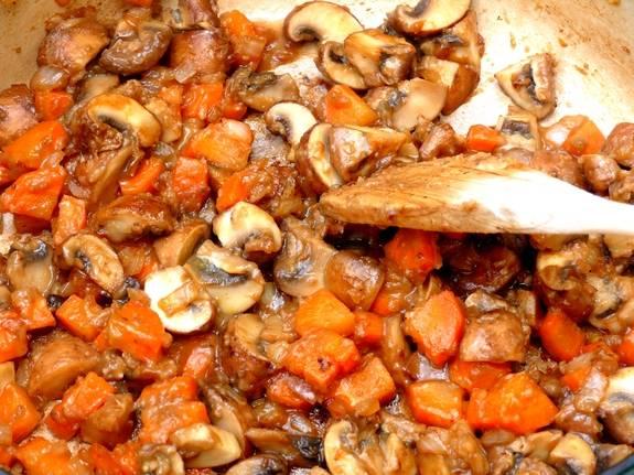 5. Овощи с грибами отправить на сковороду, в которой жарилось мясо, и обжарить около 7 минут.