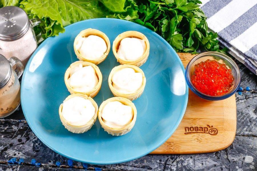 Вафельные или песочные тарталетки наполните сметаной любой жирности. По желанию сметану можете смешать с горчицей или творогом.