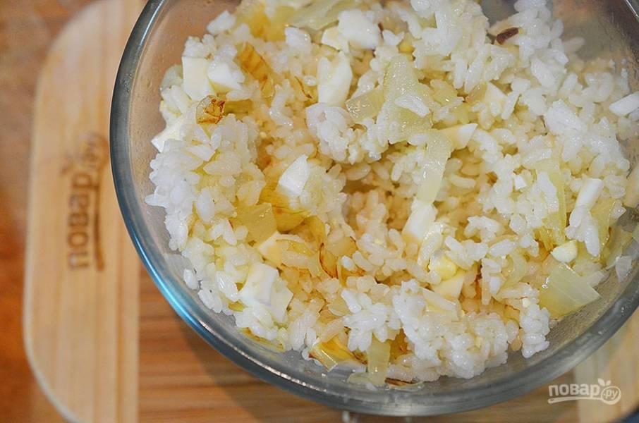 Добавьте яйца и лук к вареному рису. Перемешайте. Рисовая начинка готова.
