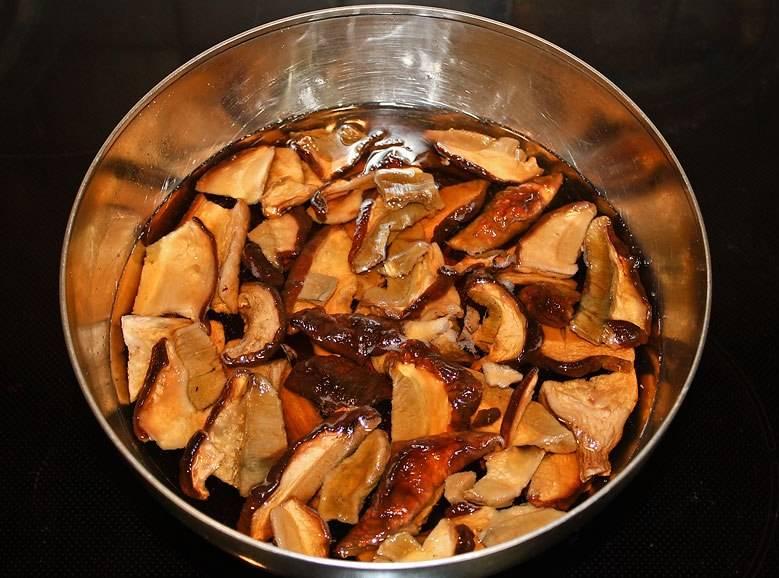 Поскольку мы здесь используем сушеные грибы, то перед тем как класть их в суп, грибы следует замочить в холодной воде на пол часика. Затем мы процеживаем воду от них через марлю и переливаем в кастрюлю, отвариваем в ней грибы в течение 30 минут. Аккуратно извлекаем грибы при помощи шумовки, а грибной бульон еще несколько раз процеживаем.