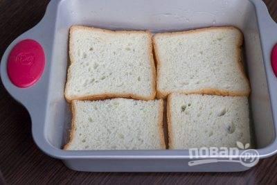 1. С тостового теста лучше срезать тонкие корочки. Уложите ломтики хлеба в глубокую форму, смазанную маслом.