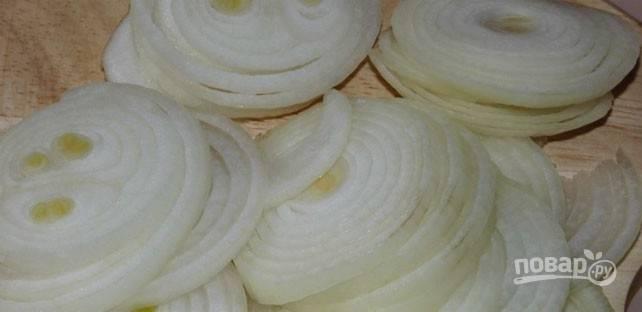 Лук почистите и нарежьте колечками. В формы для запекания распределите курицу с грибами, а сверху — лук.