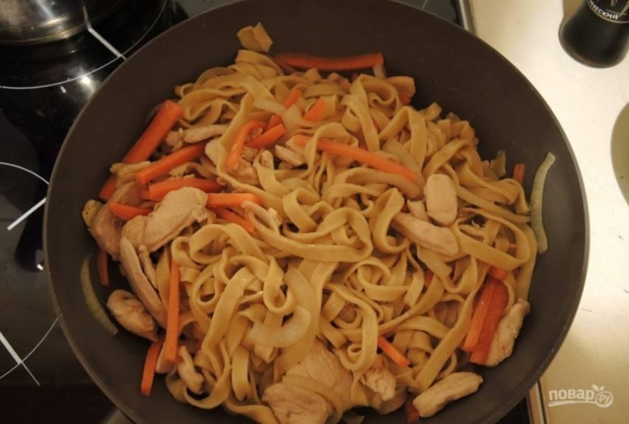 Потом выложите в сковороду лапшу и ещё влейте соевый соус.