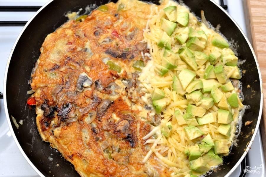 Почистите авокадо, нарежьте маленькими кусочками и положите поверх сыра.