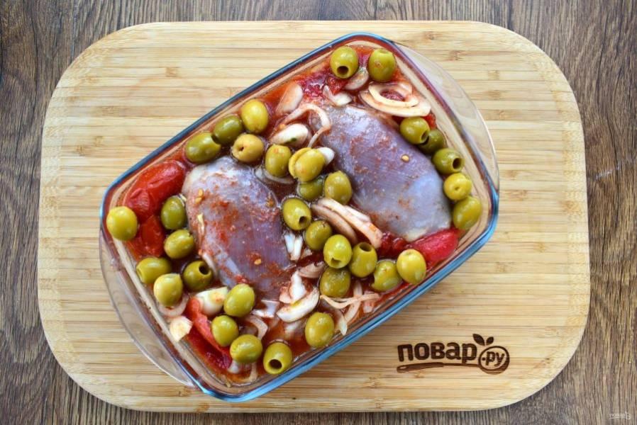 Добавьте куриные бедра и оливки, перемешайте. Переложите мясо с маринадом в форму для запекания и поставьте в разогретую до 200 °C духовку на 1 час до появления румяной корочки. За это время переверните мясо пару раз.