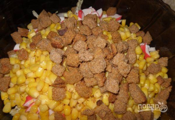 К капусте добавьте кукурузу, крабовые палочки, яйца и сухарики.
