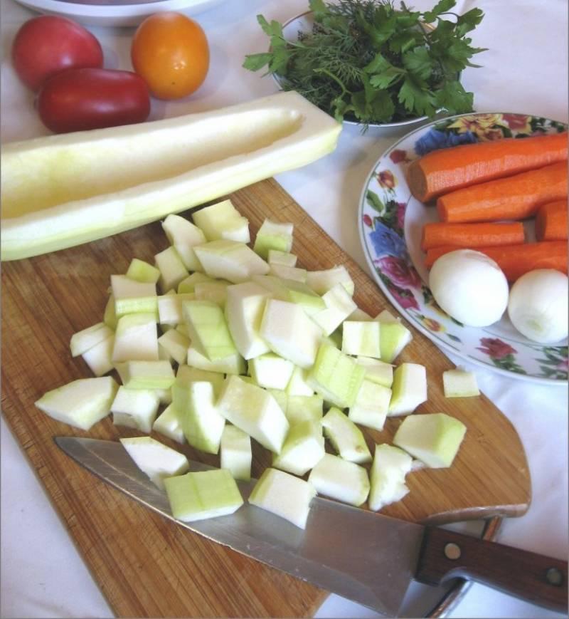 2. Сразу нарезаем мясо как на гуляш. Наливаем в чашу мультиварки полторы столовых ложек масла, размазываем и выкладываем кусочки мяса. Кабачки чистим, моем, вырезаем семечки и нарезаем кубиками.