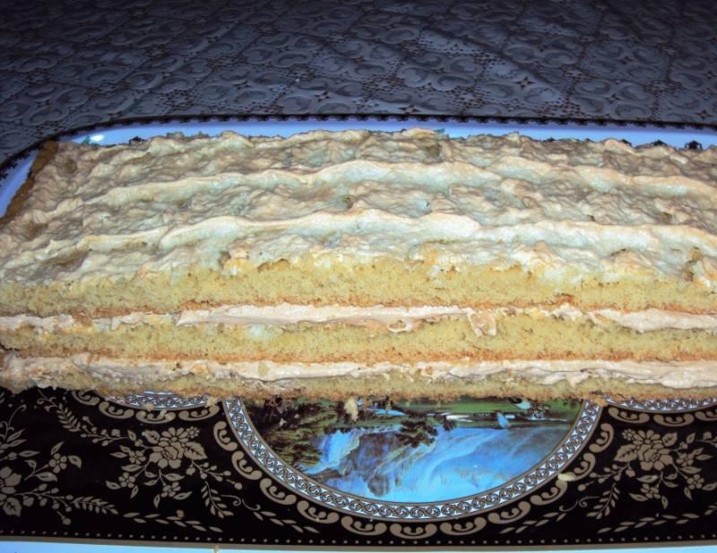 Корж разрежьте на 3 части. Первую смажьте половиной крема, накройте второй частью, выложите остальной крем и сверху третью часть коржа.