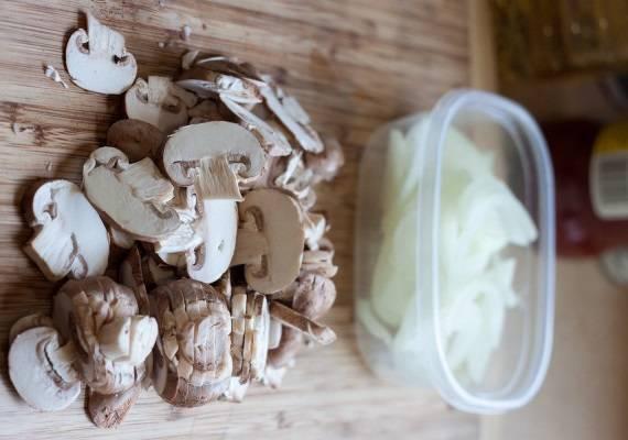 3. Очистить и нарезать тонкими полукольцами лук. Шампиньоны вымыть, обсушить и нарезать ломтиками. В рецепт приготовления свинины, запеченной с грибами можно использовать не только шампиньоны, но и любые другие грибочки по вкусу.