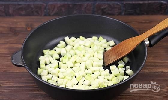 2. На отдельную сковороду с маслом отправьте нарезанные кубиками кабачки. Если они не очень молодые, лучше снять кожицу.
