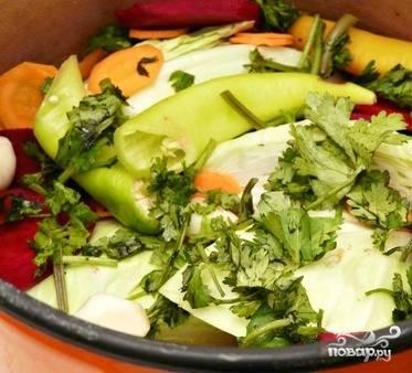 4. В кастрюлю укладываем слоями сначала листы капусты, затем — куски капусты, свеклу, остальные овощи и рубленую кинзу, а сверху выкладываем листья капусты.