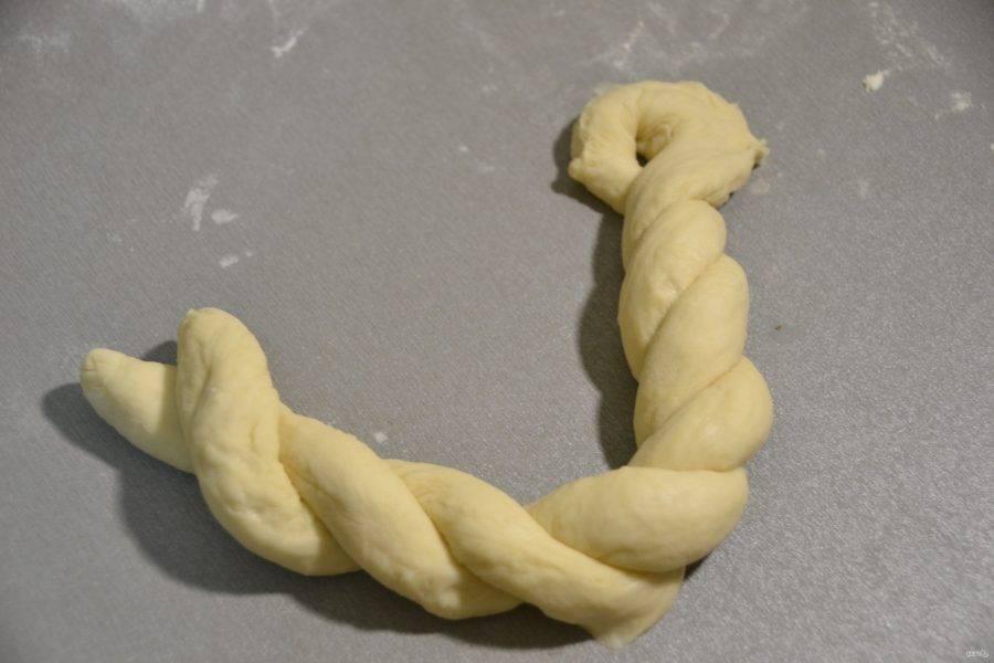 Вытянутое тесто переплетите в жгутик, оставляя небольшое отверстие в месте сгиба.