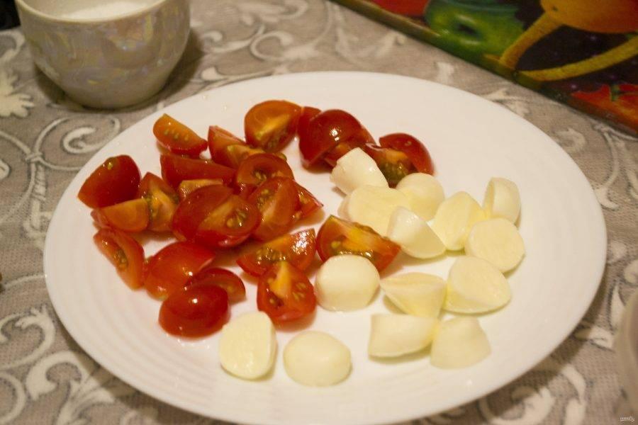 Для начала нам необходимо нарезать помидоры черри на 4 части, а кусочки сыра моцарелла на 2 части.