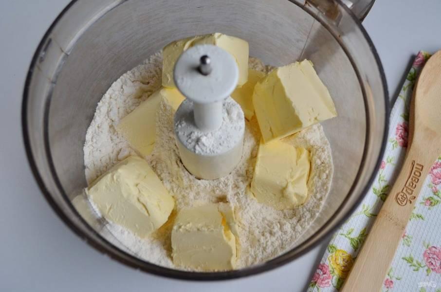 В чашу измельчителя всыпьте просеянную муку, положите щепотку соли и маргарин. Если нет измельчителя, то высыпайте муку прямо на стол, сверху кубики маргарина и ножом рубите, пока не получится мелкая крошка.