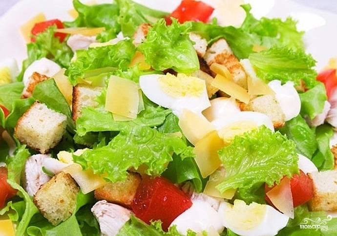 В отдельной миске перемешать кусочки консервированных ананасов, нарезанную ломтиками курицу и сухарики. Переложить в посуду с салатными листьями и еще раз перемешать. Полить соусом, посыпать тертым пармезаном и сразу подать на стол.