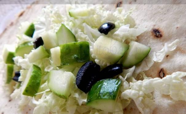 Выкладываем на край лаваша капусту, сверху кладем маслины и огурец.
