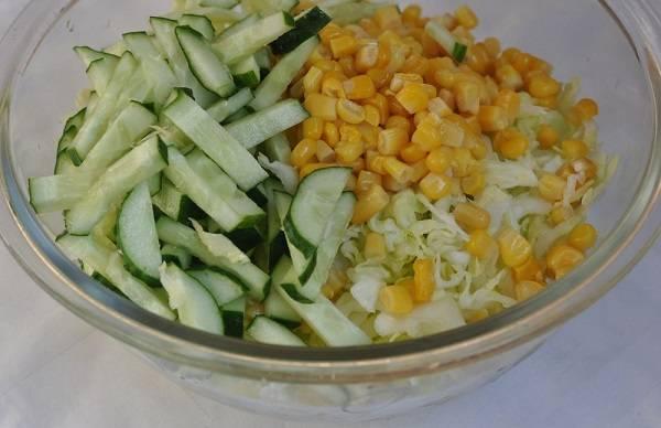 4. В салатник выложить огурец и кукурузу, предварительно слив с нее жидкость. В рецепт приготовления простого салата с кукурузой консервированной можно использовать также самую разнообразную свежую зелень.