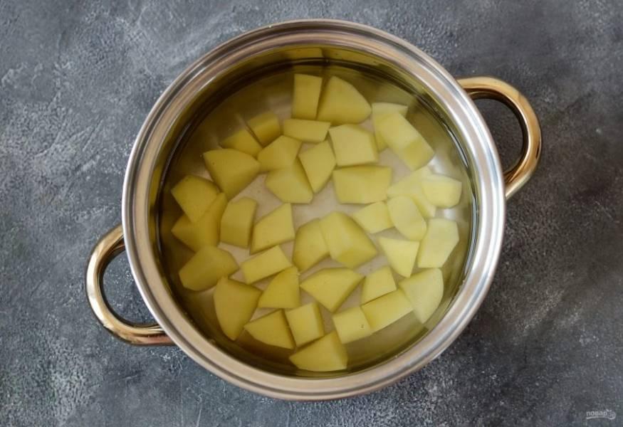 Картофель нарежьте кубиками. Налейте воду в кастрюлю.