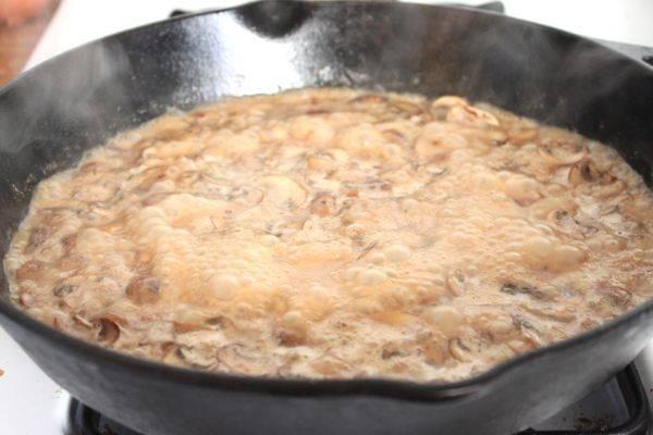 4. Луковицу очистить и нарезать мелким кубиком. Отправить на сковороду к грибам и жарить до золотистого цвета. Затем добавить сметану и бульон.