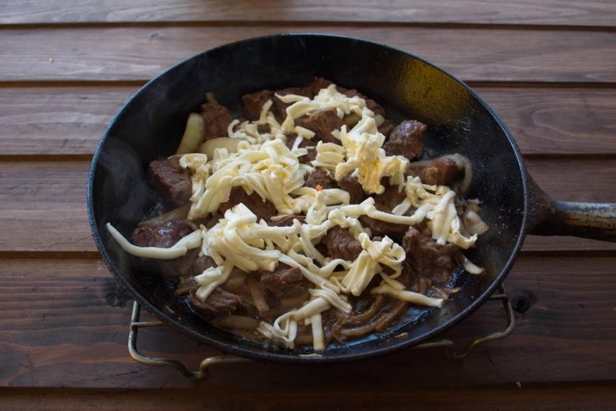 Влейте немного воды (5-6 ст. ложек). Накройте сковороду крышкой и тушите 5 минут. За это время натрите на терке плавленый сырок. Снимите крышку и выложите сырок сверху на мясо. Поставьте сковороду в духовку (сковорода должна быть без пластиковых-деревянных ручек). Запекайте в духовке 8 минут. Подайте к столу.
