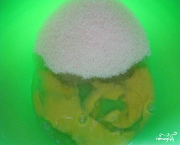 2.Возьмите глубокую миску, вбейте яйца, добавьте сахарный песок и тщательно взбейте миксером или венчиком до образования пены. Включите духовой шкаф для нагрева до 180 градусов.