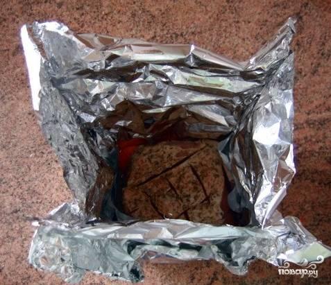 Поверх овощей кладите мясо, старательно заверните его в фольгу. Это нужно сделать аккуратно, чтобы была возможность развернуть конверт для проверки готовности блюда. Совет: сначала герметично закройте боковые швы, выдавите из конверта воздух снизу-вверх, соедините и закручивайте верхние края фольги.