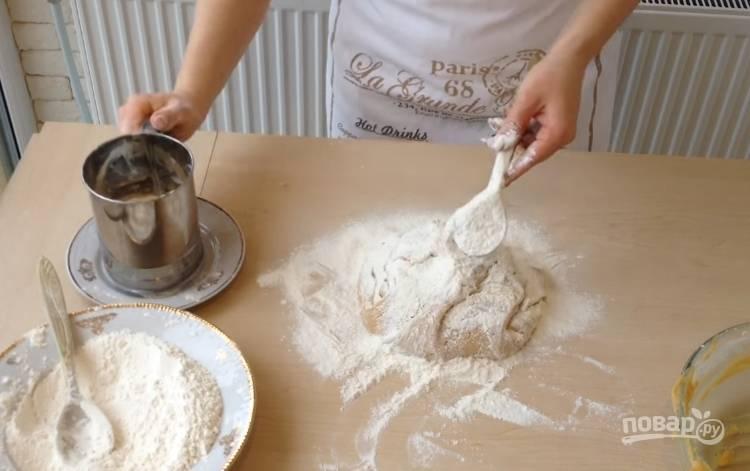 7.Небольшую часть оставшейся муки высыпаете на стол, выкладываете липкое тесто и постепенно добавляете оставшуюся муку, замешиваете тесто.