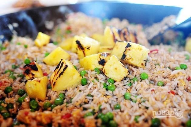 16. На сковороду с рисом добавьте ананас, предварительно нарезав его средними кусочками.