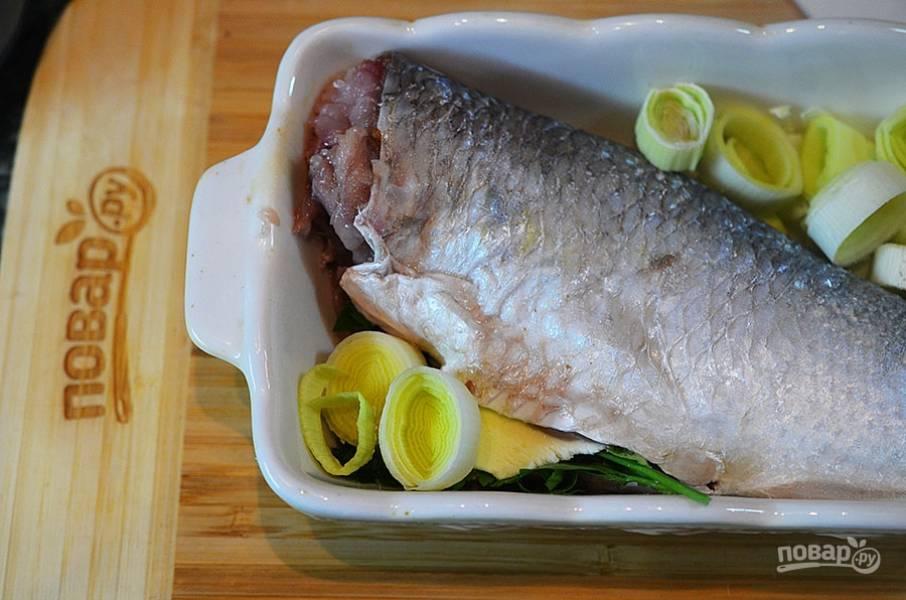 4. Выложите рыбу в смазанную маслом форму. Вокруг выложите кольца порея. Посолите и поперчите.