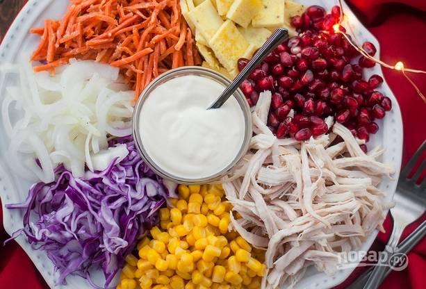7. Обсушите лук, выложите на тарелку. Рядом — капусту, кукурузу, курочку, зерна граната, омлет, морковь по-корейски. В центре поставьте заправку. Подавайте салатик к столу.