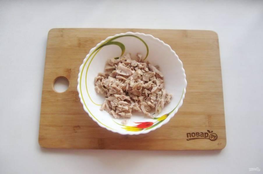 Отделите мясо от костей и шкурки, мелко нарежьте и разложите по тарелкам.