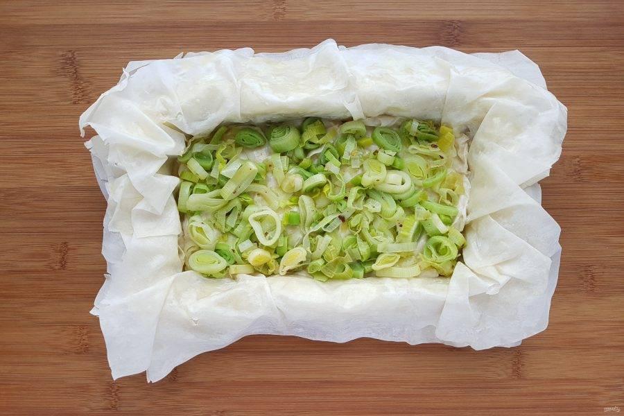 Сверху равномерно распределите лук порей. Посыпьте небольшим количеством сыра.