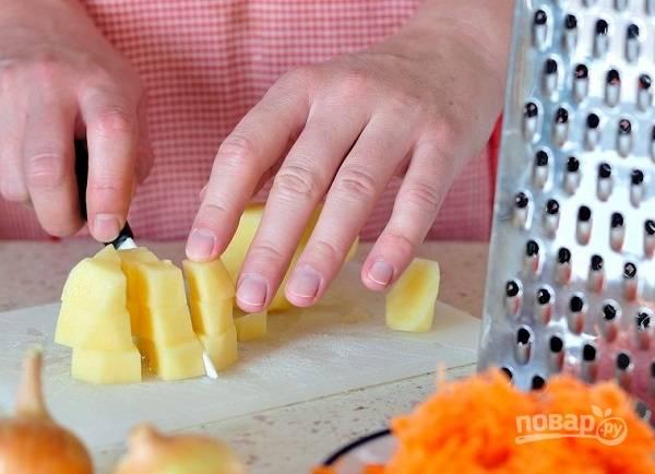 2. Очистите картофель и нарежьте мелкими кубиками. Морковь натрите на терке, лук измельчите.