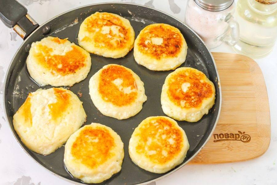 Обжарьте сырники с одной стороны около 2 минут на умеренном нагреве и аккуратно переверните на другую сторону. Помните, что в них нет муки и они очень нежные, поэтому могут расползтись по сковороде. Обжарьте еще 2 минуты.