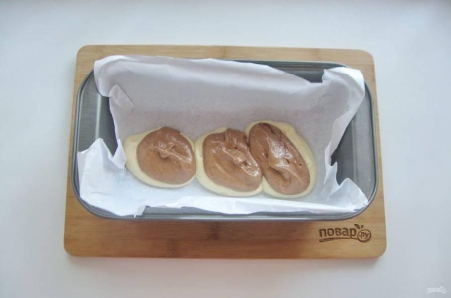 В форму для кекса поочередно выкладывайте светлое и темное тесто.