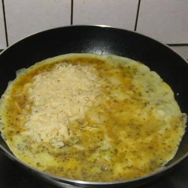 Разогрейте масло в сковороде. Залейте яичную смесь. Через 30 секунд смешайте еще раз но уже в самой сковороде. Равномерно посыпать тертым сыром.