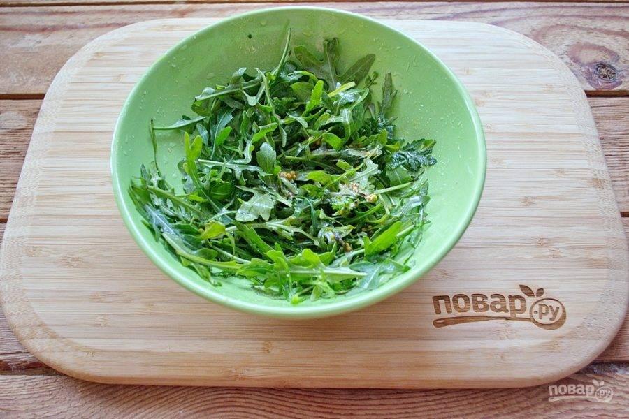 Смешайте несколько ложек растительного масла, 0,5 чайной ложки горчицы с зернами, небольшую щепотку соли и пару капель лимонного сока. Перемешайте заправку для салата, заправьте ею рукколу. Перемешайте так, чтобы заправка распределилась по всей рукколе.