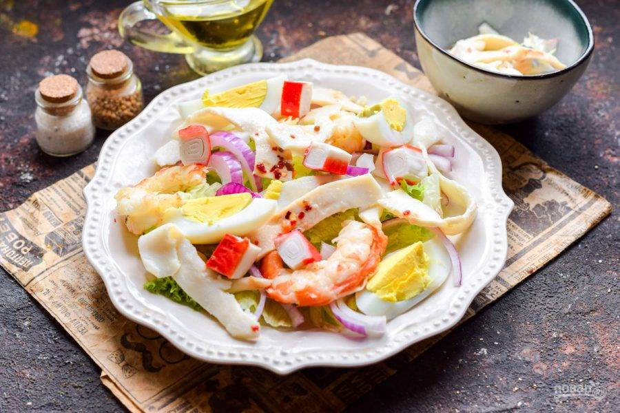 Добавьте в салат нарезанные крабовые палочки и вареное яйцо, разделенное на 4 дольки. Заправьте салат маслом, добавьте соль и перец.
