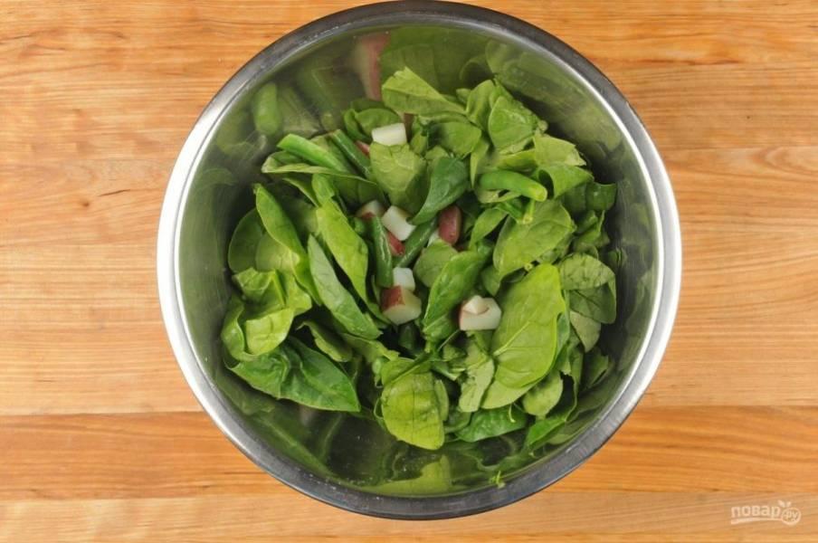5. Теперь сделайте тёплый салат. Смешайте шпинат с фасолью, картофелем, соком лимона, маслом, солью, чесноком и перцем.