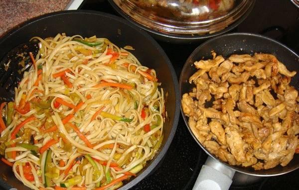 6. Когда курица начнет покрываться золотистой корочкой, добавляем в нее соевый соус и тушим, пока не выпарится лишняя жидкость. А готовую лапшу тем временем смешиваем с овощами и жарим около 5 минут на слабом огне.