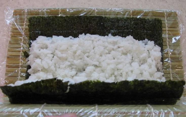 Застелите бамбуковый коврик пищевой пленкой. Выложите на коврик один лист нори. Мокрыми руками равномерно распределите рис (1 см. до края оставьте свободным). Ловким движением переверните лист нори, чтобы рис оказался снизу.