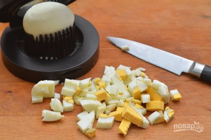 Отваренные яйца почистите и также нарежьте мелким кубиком.