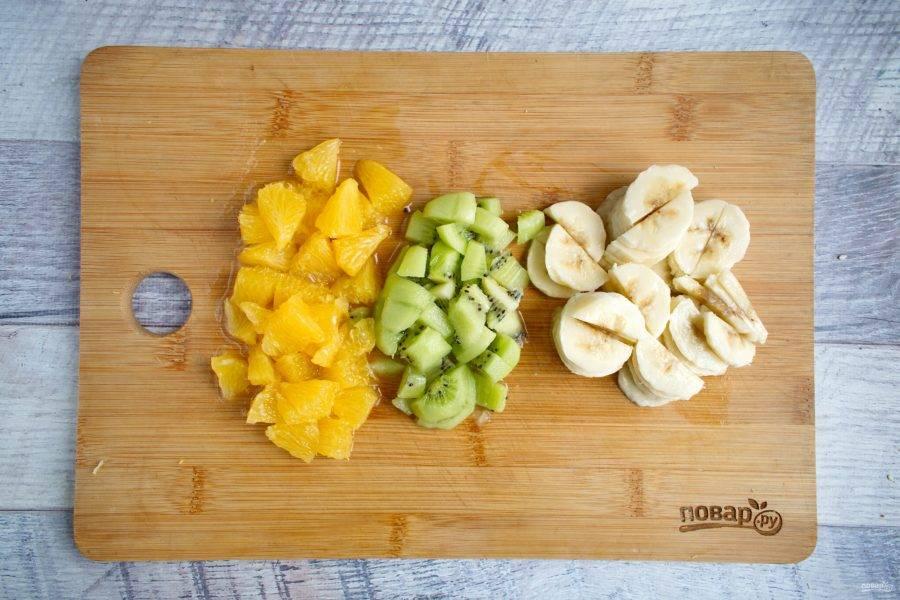 Фрукты очистите, апельсин очистите от пленок. Все фрукты нарежьте на мелкие кубики. Лишний сок с фруктов слейте.