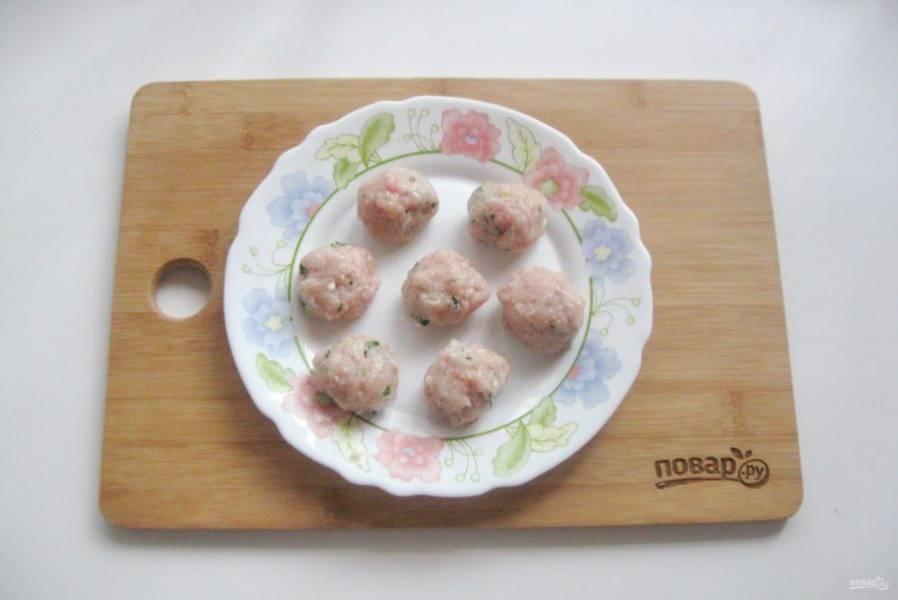 Мясной фарш посолите по вкусу, добавьте зелень. Сформируйте маленькие шарики — фрикадельки.